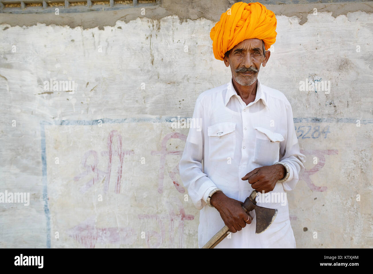 Old indian man in white outfit wearing orange turban, standing in front of white wall in a village near Pushkar, - Stock Image