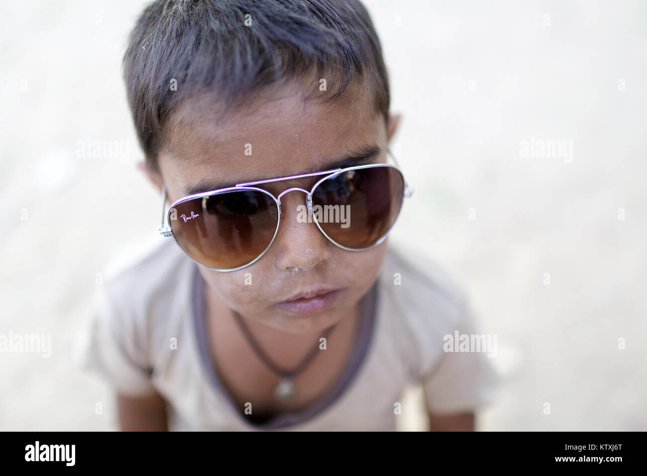 Small indian boy wearing oversized sunglasses, Village near Pushkar, Rajasthan, India. - Stock Image