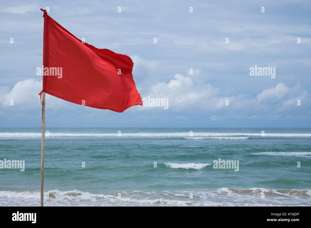 A red warning flag on the beach in the Nuca Dua Bali - Stock Image