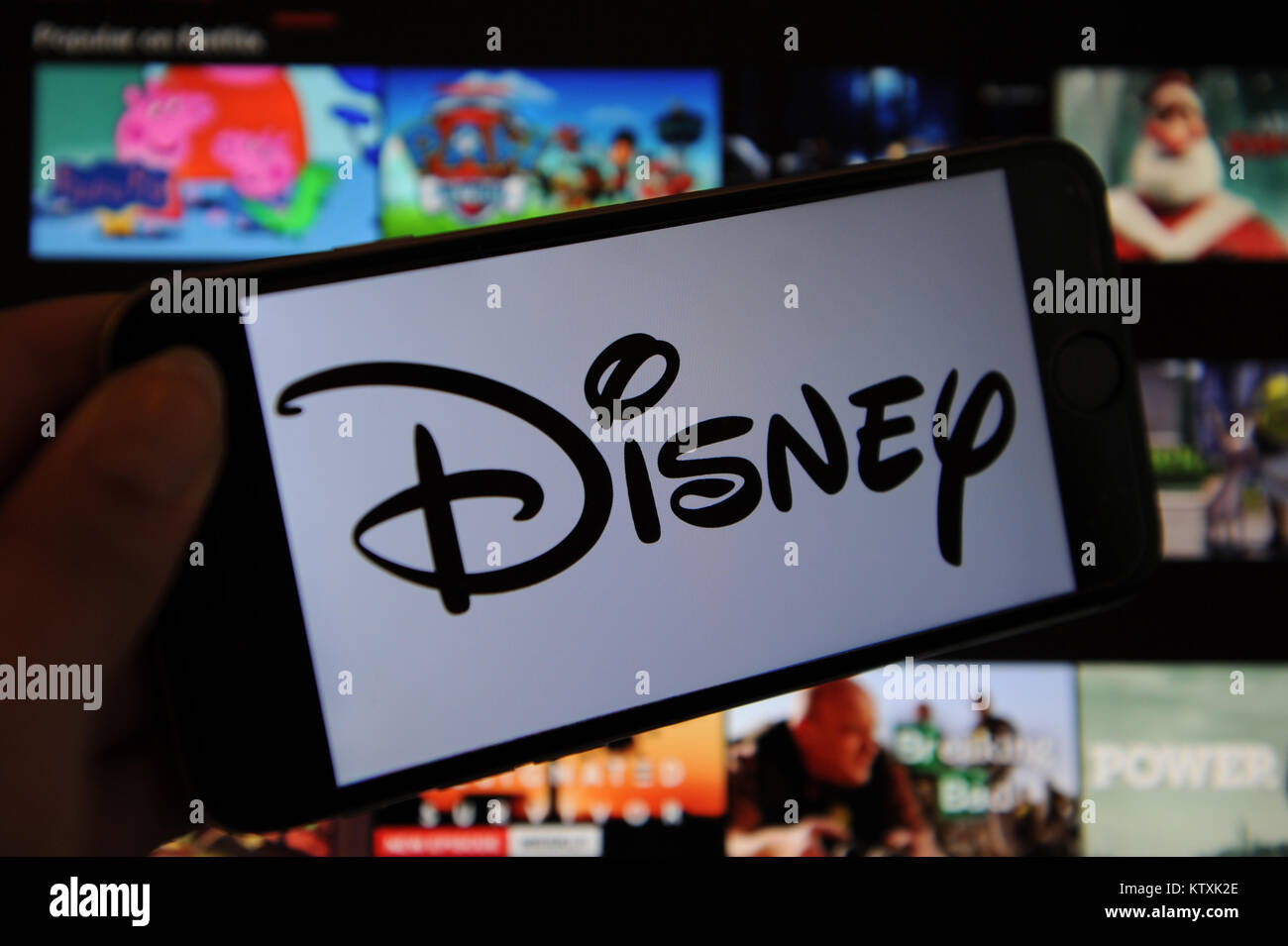 A Disney logo on a phone screen and Netflix on a computer screen Stock Photo
