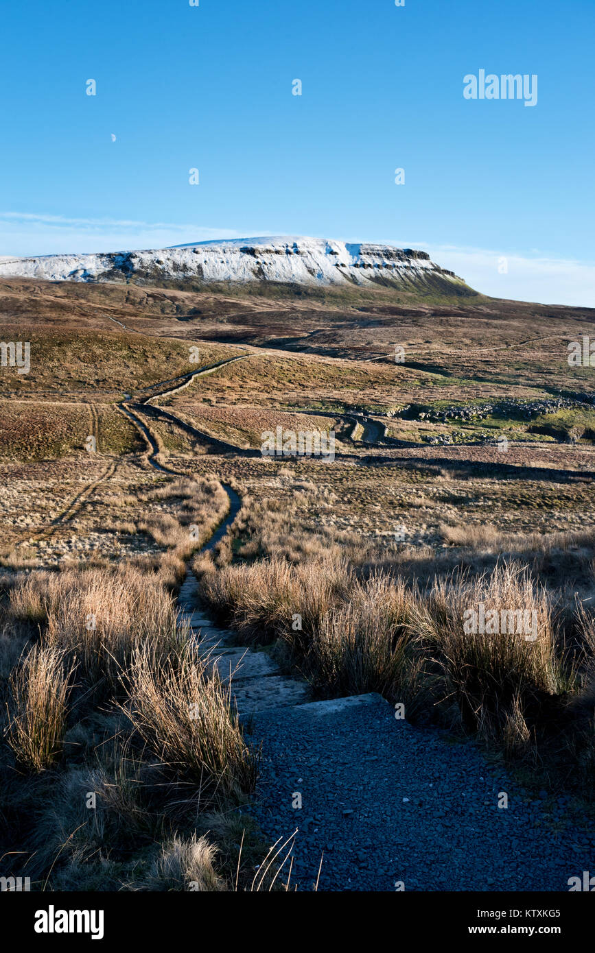 The moon rises over a snow-capped Pen-y-ghent hill seen from the Three-Peaks footpath to the west. Near Horton-in - Stock Image
