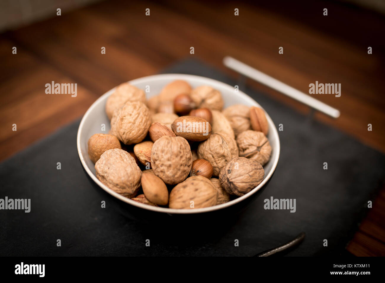 A bowl of mixed whole nuts in their shells including walnuts, hazelnuts, almonds and pecans with a short depth of - Stock Image