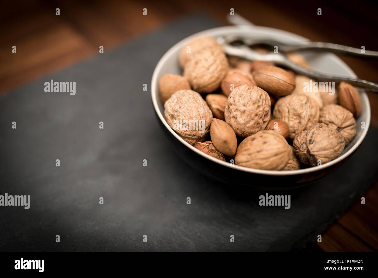 A bowl of mixed whole nuts in their shells including walnuts, hazelnuts, almonds and pecans with a nut cracker - Stock Image