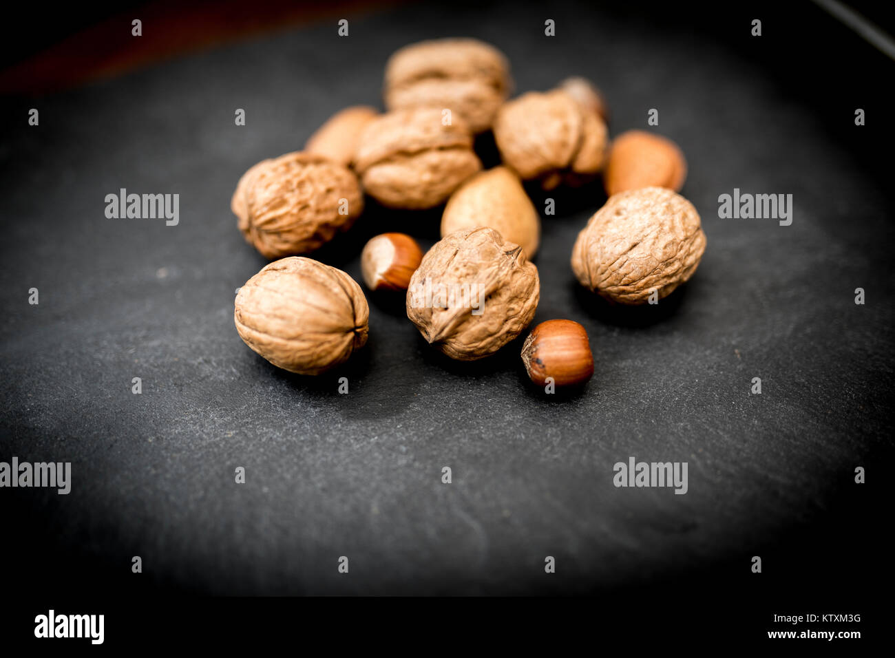 Mixed whole nuts in their shells including walnuts, hazelnuts, almonds and pecans shot on black slate - Stock Image