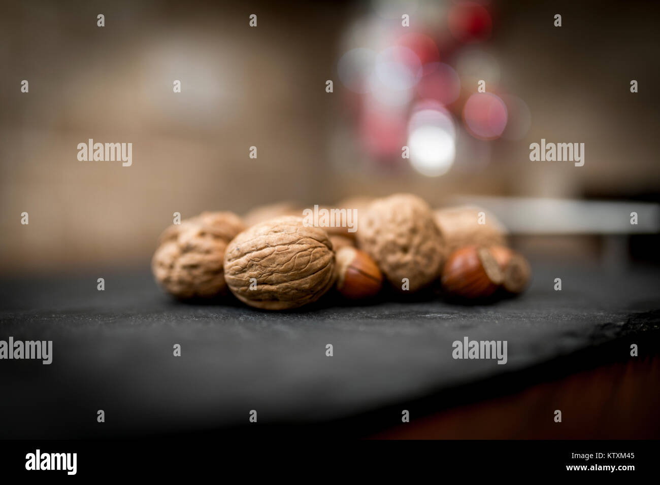 Mixed whole nuts in their shells including walnuts, hazelnuts, almonds and pecans with a short depth of field - Stock Image