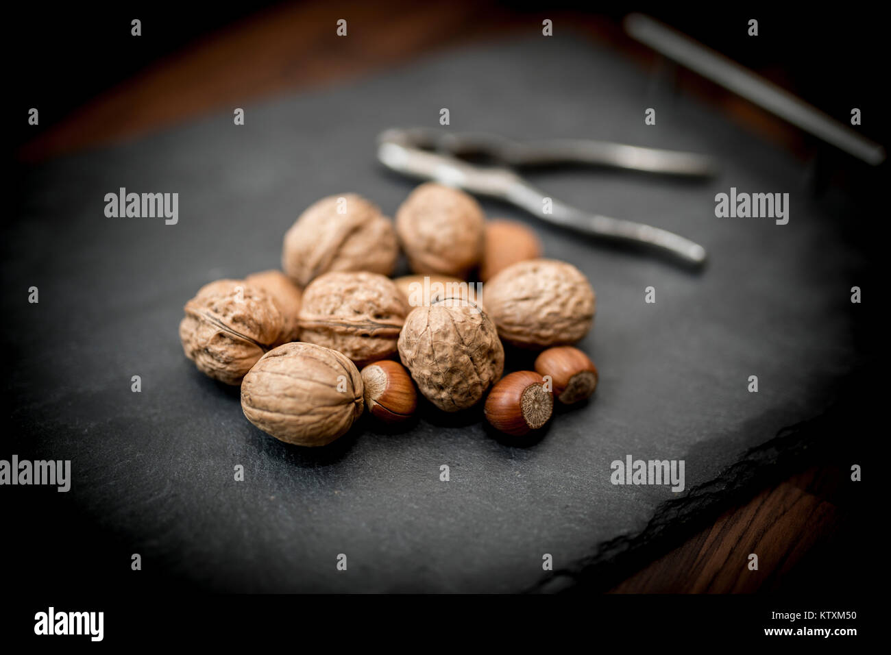Mixed whole nuts in their shells including walnuts, hazelnuts, almonds and pecans with a nut cracker - Stock Image