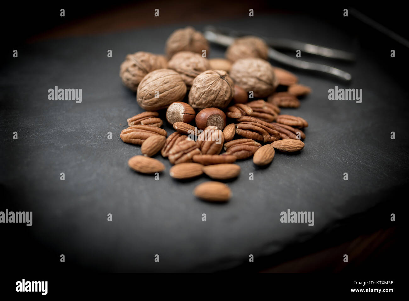 A healthy selection of mixed whole and shelled nuts including walnuts, hazelnuts, almonds and pecans with a nut - Stock Image