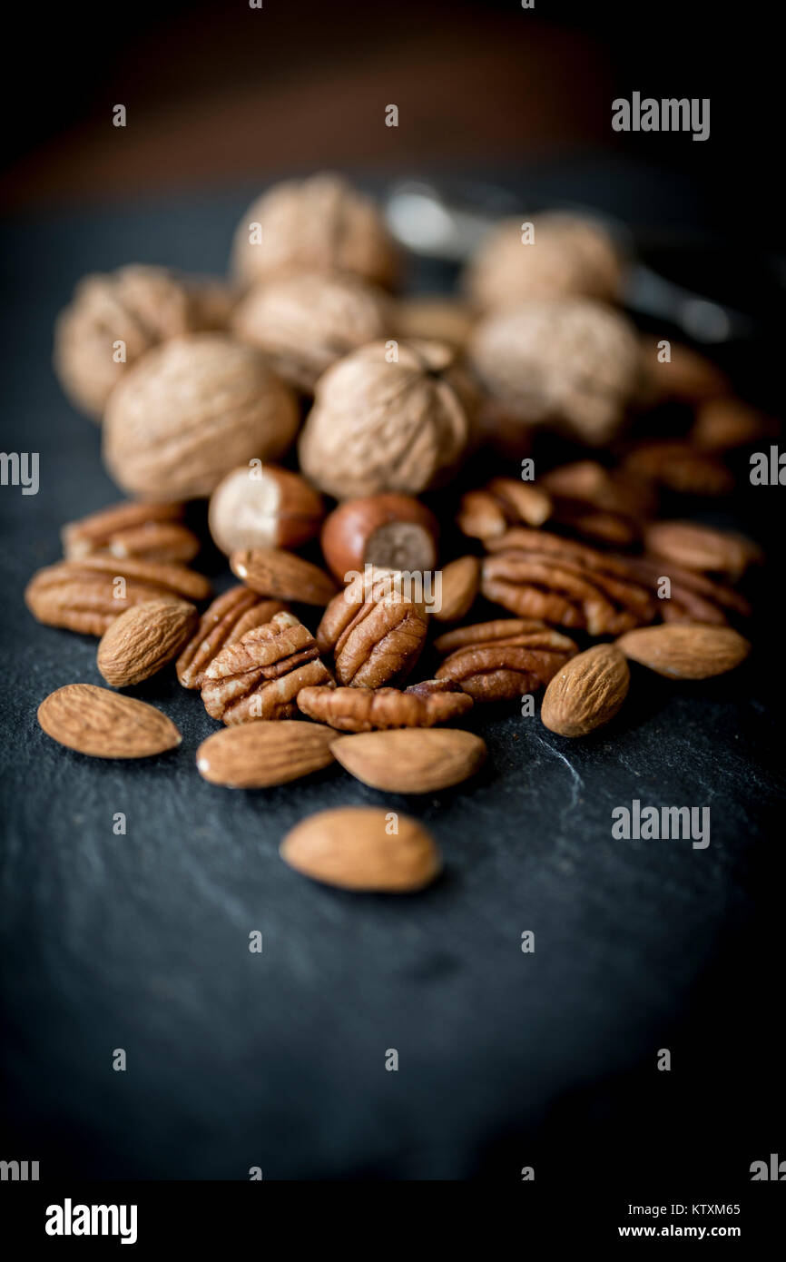 A selection of healthy mixed whole and shelled nuts including walnuts, hazelnuts, almonds and pecans with a short - Stock Image