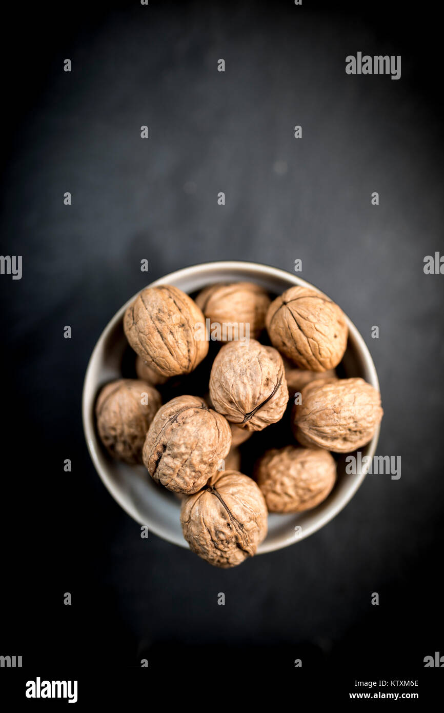 A bowl of whole walnuts in their shells in a bowl shot from above on a natural black slate background - Stock Image