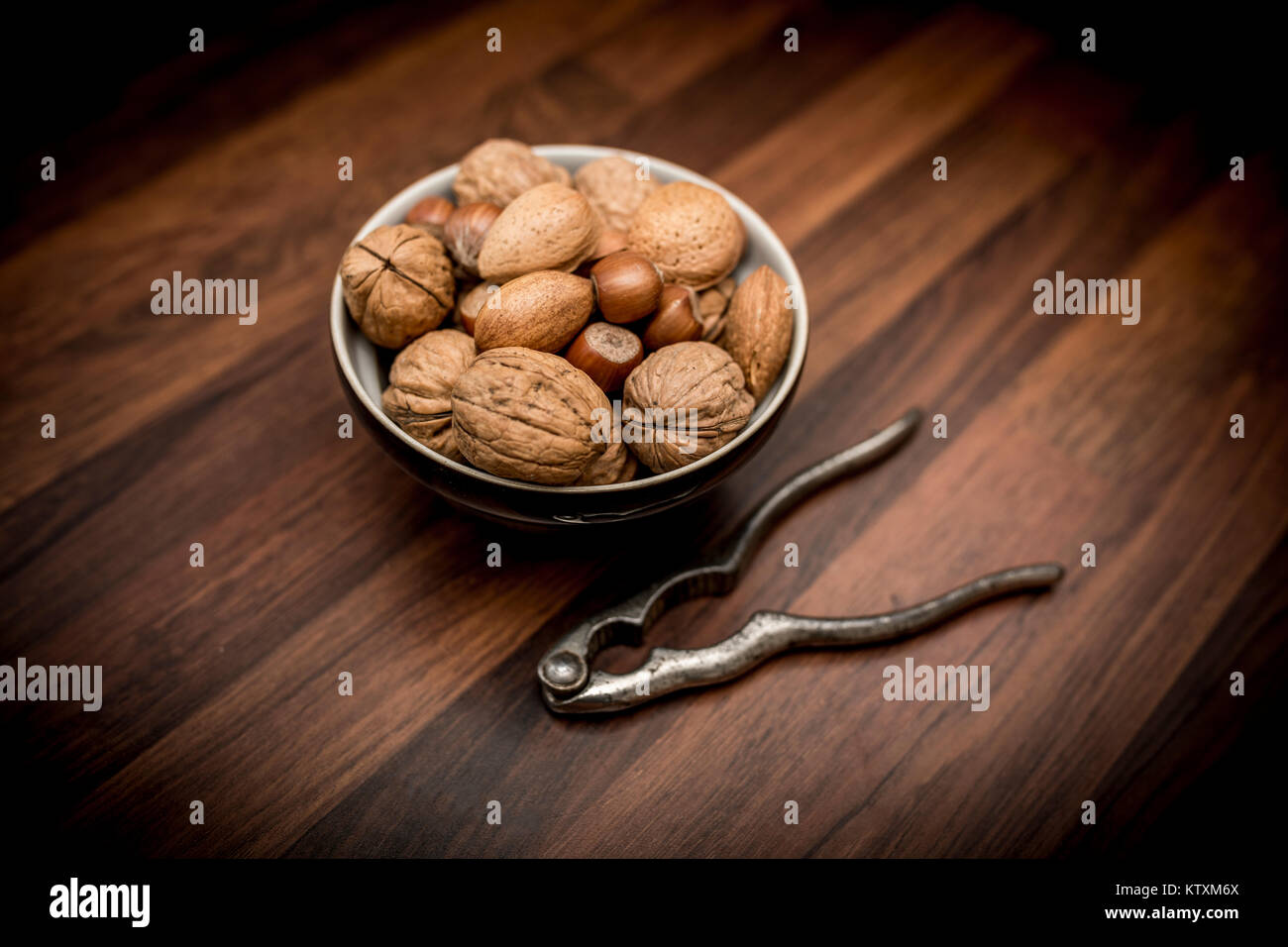 A bowl of mixed whole nuts in their shells including walnuts, hazelnuts, almonds and pecans with nut cracker - Stock Image