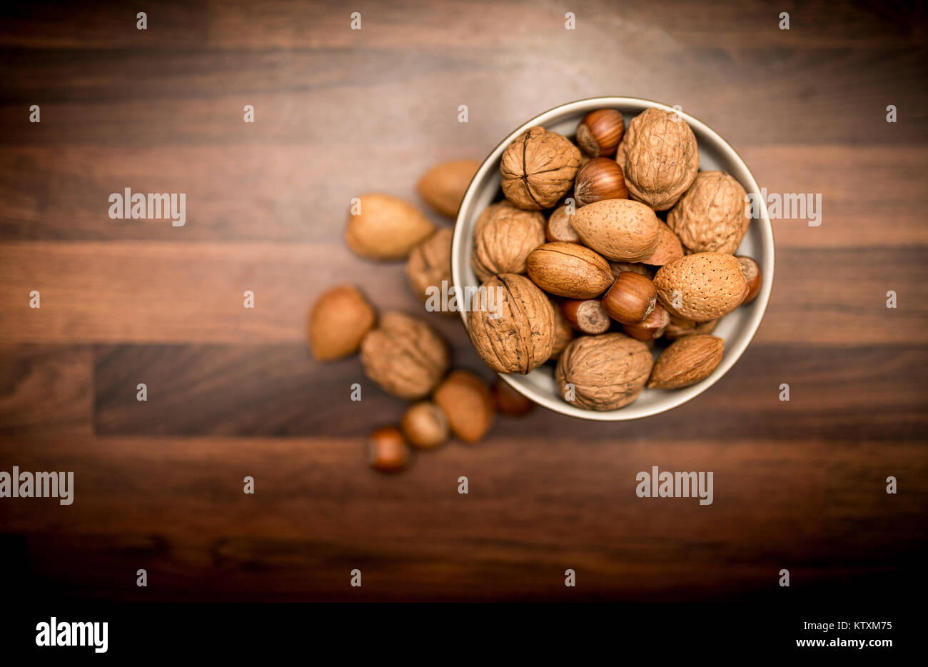 A bowl of healthy mixed whole nuts in their shells including walnuts, hazelnuts, almonds and pecans shot from above - Stock Image
