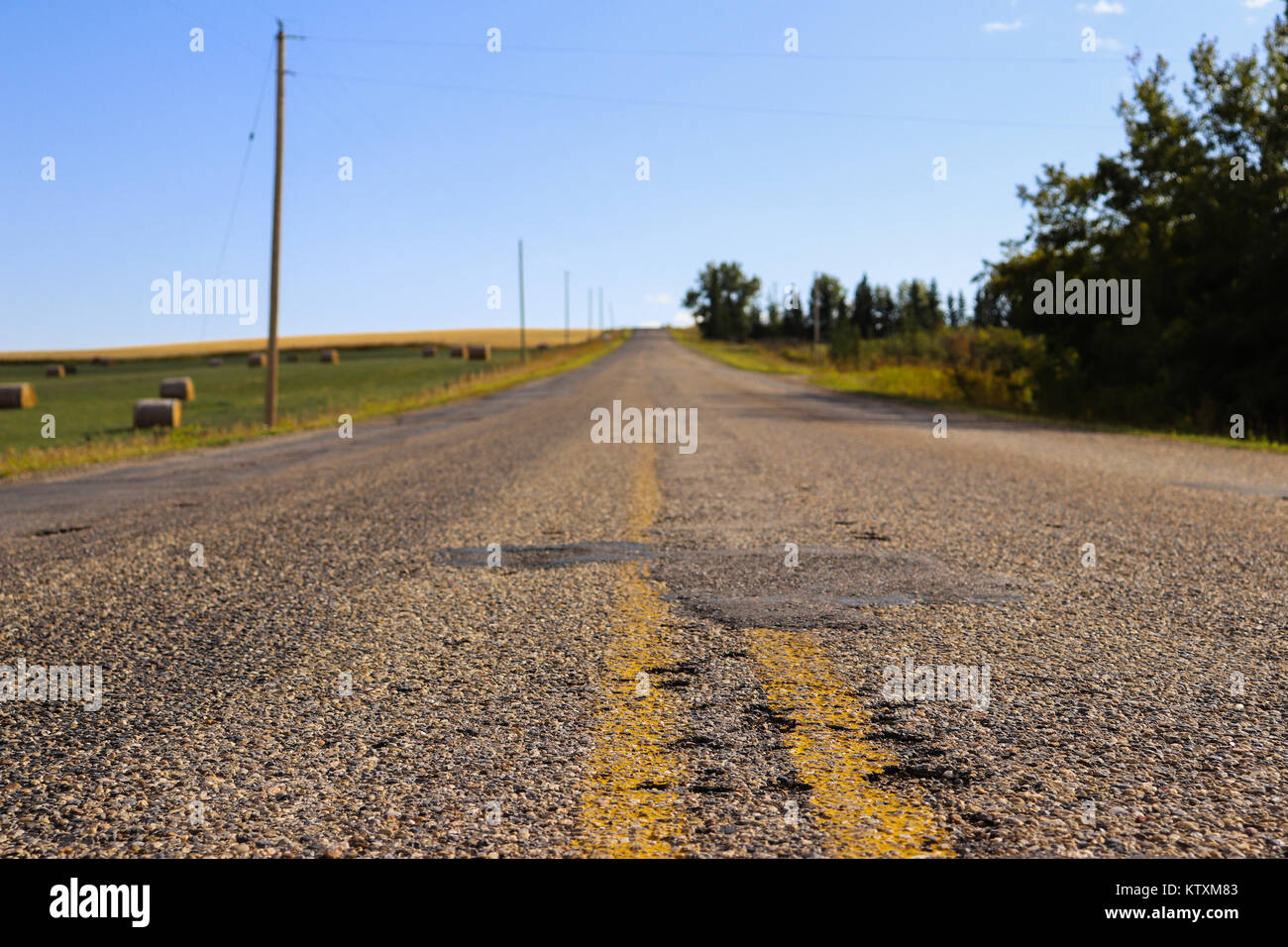 Old road going into the distance with a farm to the side and a blue sky above - Stock Image