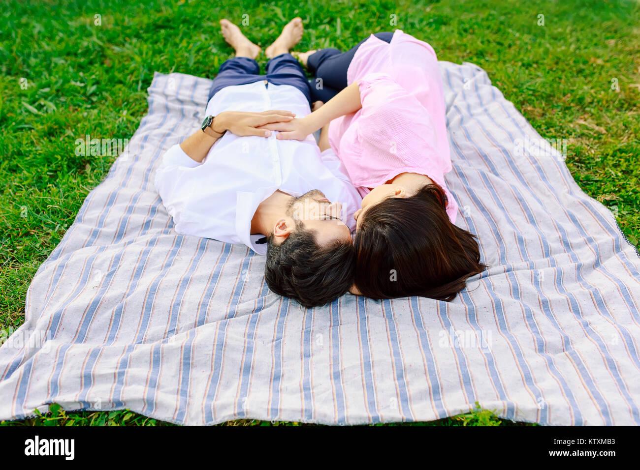 Young loving couple lying together enjoying closeness - Stock Image