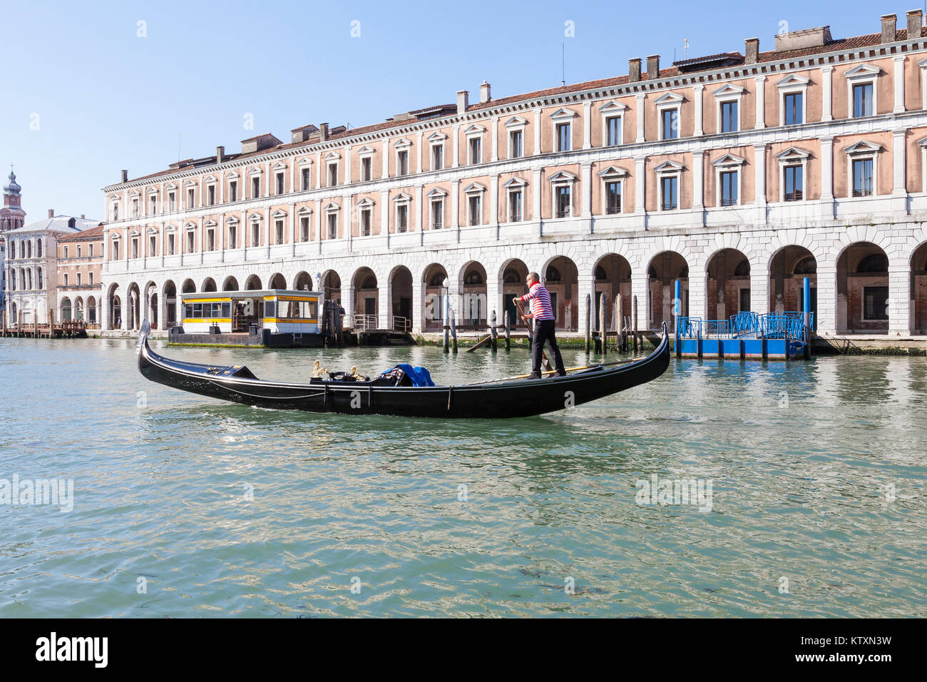 Gondolier rowing a gondola  on the Grand Canal at Rialto Mercato, San Polo, Venice, Italy - Stock Image