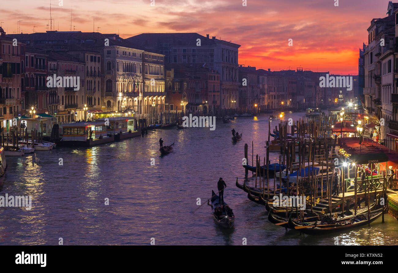 Gondolas on the Grand Canal at sunset from Rialto Bridge, Venice, Italy with light winter mist, dusk, night scene - Stock Image