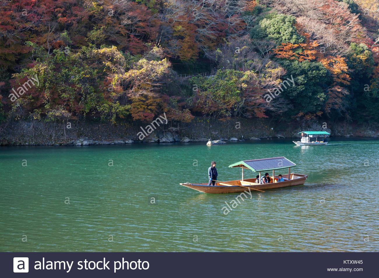 Arashiyama, JAPAN - NOVEMBER 28, 2017: Unidentified sailors sail wooden boat to bring tourist people to enjoy autumn - Stock Image