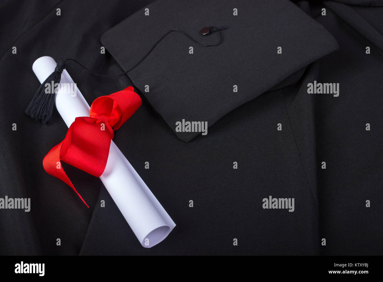 Graduation Day. A gown, graduation cap, and diploma and laid out ready for graduation day. - Stock Image