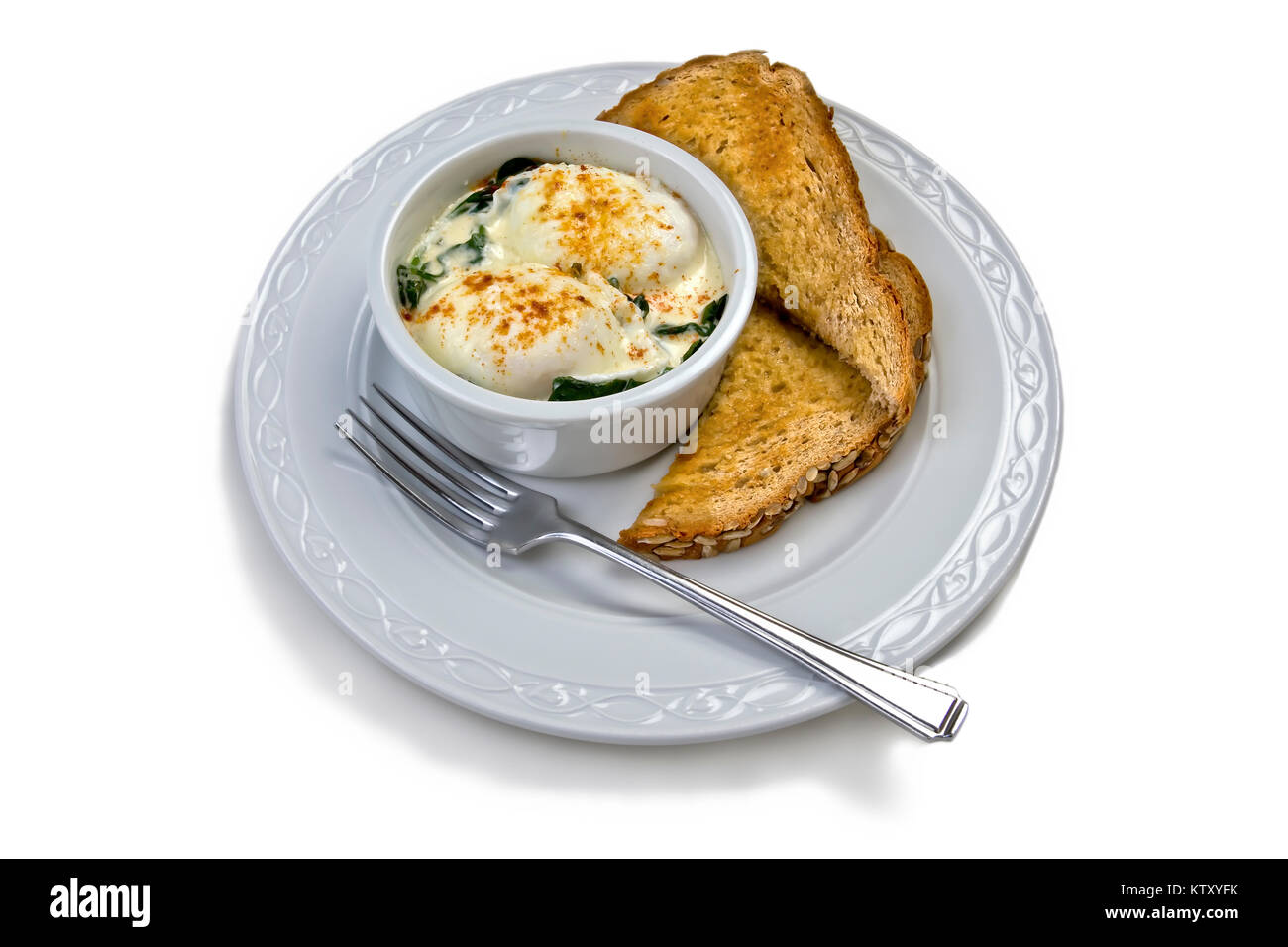 Eggs Florentine with poached eggs on a bed of wilted spinach topped with Hollandaise sauce and dusted with Paprika - Stock Image