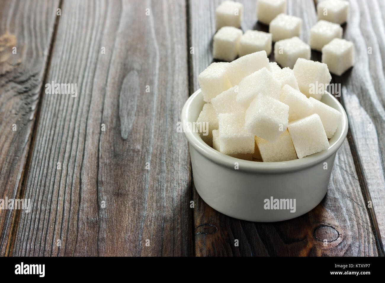White sugar in bowl on wooden background. Selective focus, horizontal. A few sugar cubes are near the full glass - Stock Image