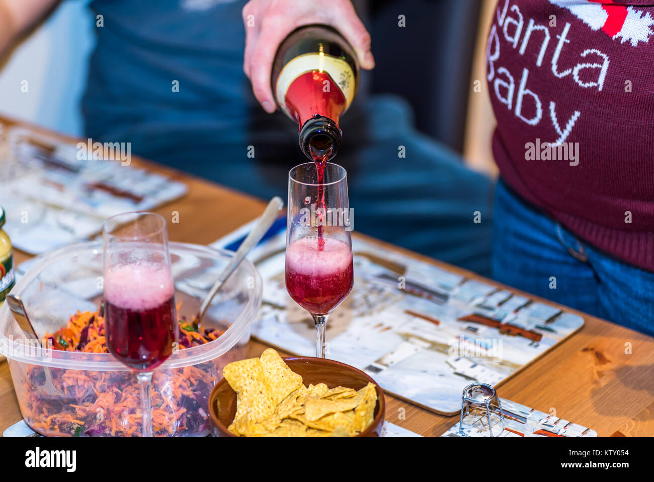 Pregnant female in christmas pullover holding bottle and pouring red non alcoholic wine into champagne glass on - Stock Image