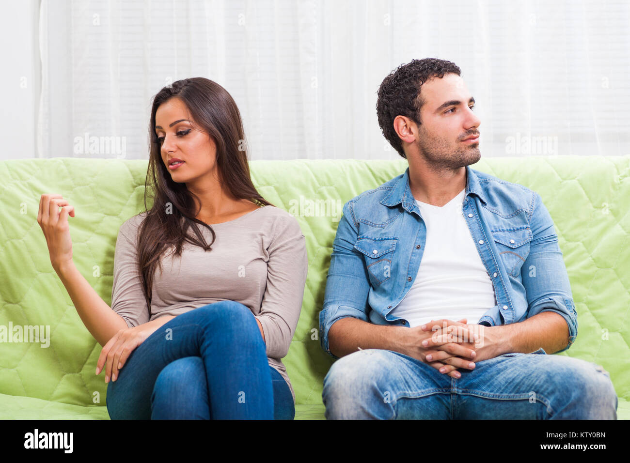 Young couple is sitting on sofa at home and they are getting bored. - Stock Image