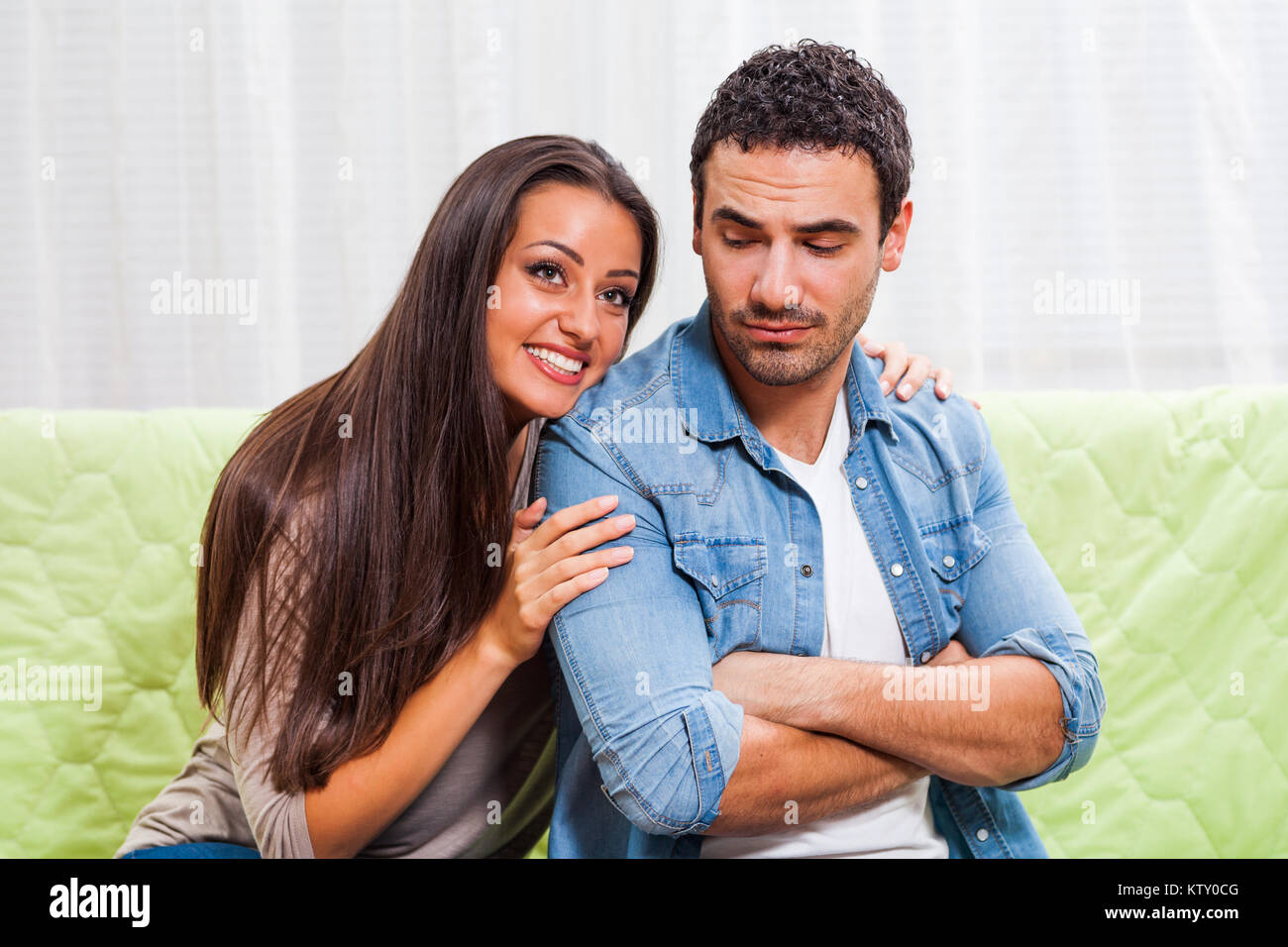 Young couple is sitting on sofa at home. Man is angry. - Stock Image