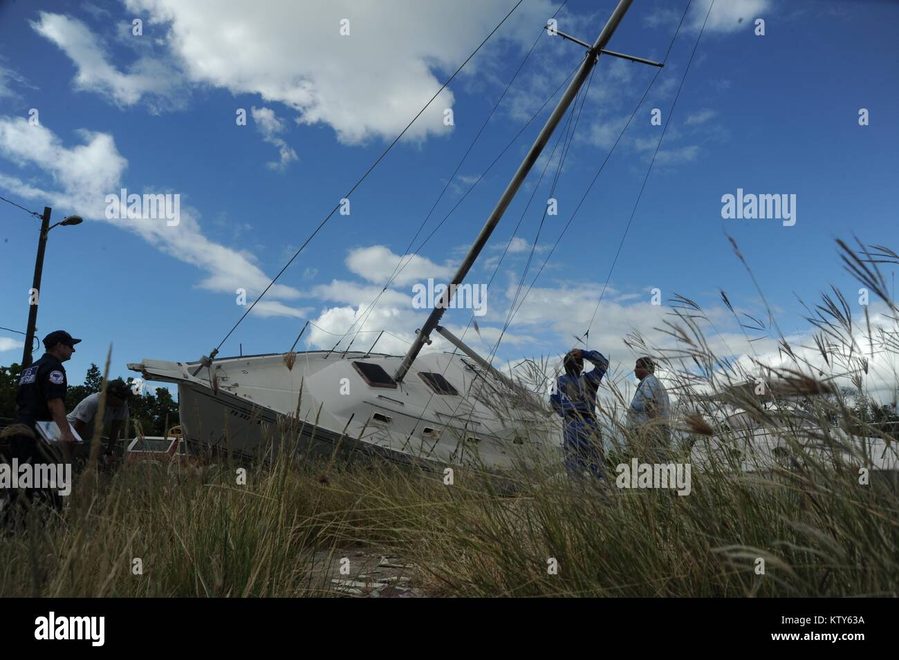 U.S. Coast Guard officers remove a wrecked sailboat in the aftermath of Hurricane Maria December 19, 2017 in Salinas, - Stock Image