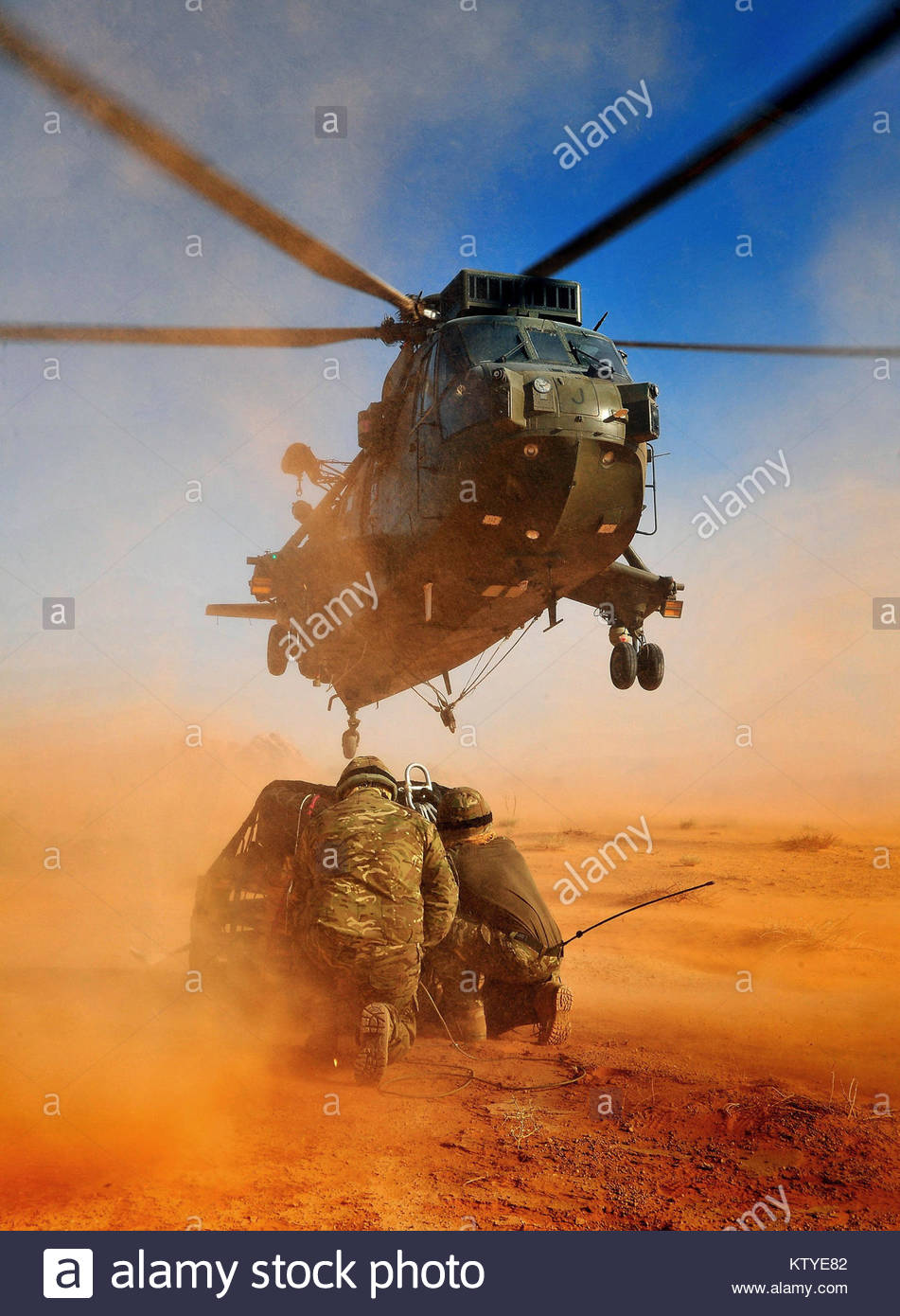 Royal Marines from the Commando Mobile Air Operations Team conducting load lifting operations with a SeaKing Mk4 - Stock Image