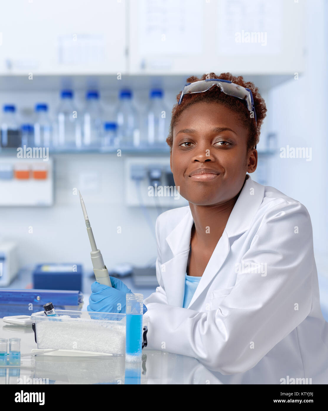 African-american scientist or graduate student in lab coat and protective gloves smiles at the camera - Stock Image