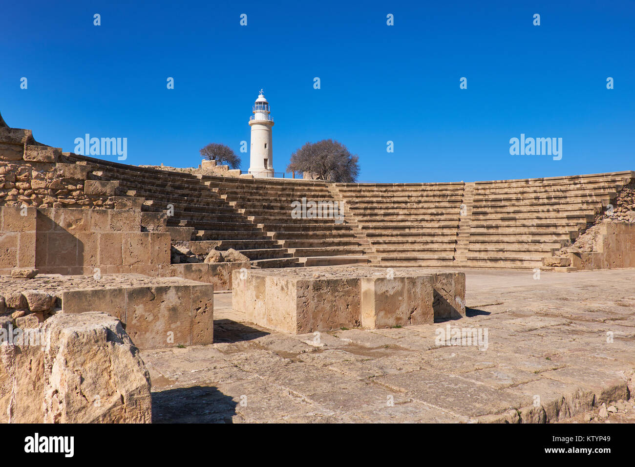 Ancient Greek amphitheater in archaeological site in Paphos, Cyprus, with a white lighthouse on the back Stock Photo