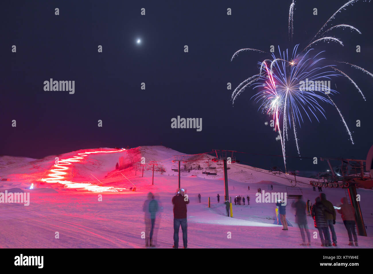 The Sun Valley Torchlight Parade:  A bunch of skiers descend down Dollar Mountain with road flares, making a winding - Stock Image