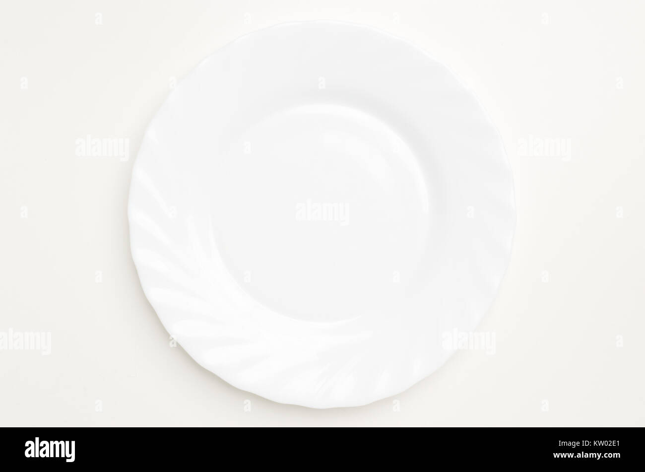 Empty white isolated plate on white table. - Stock Image