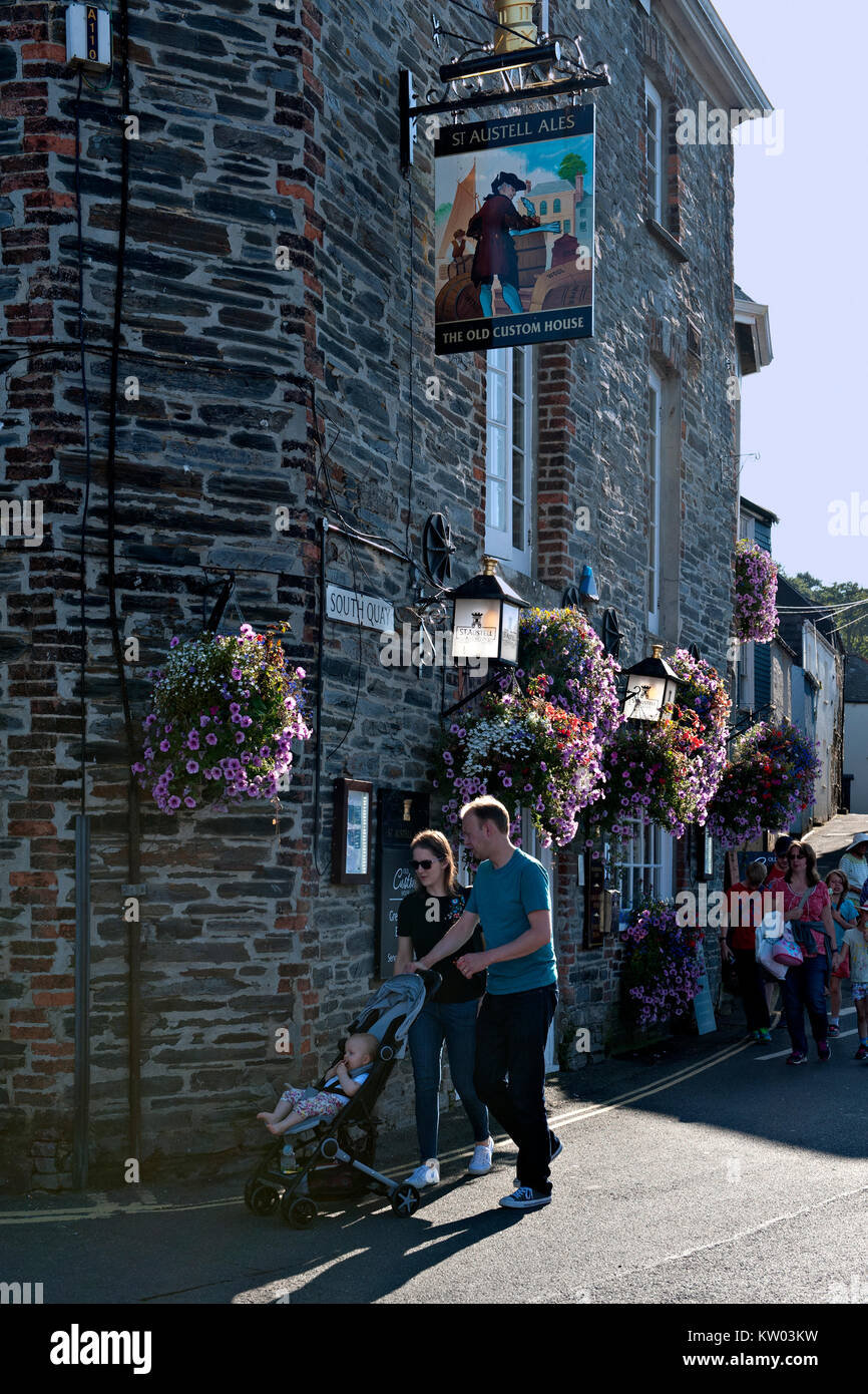 TA Couple pushing a small child in a pushchair pass The Old Custom House public house in Padstow, Cornwall. UK Stock Photo
