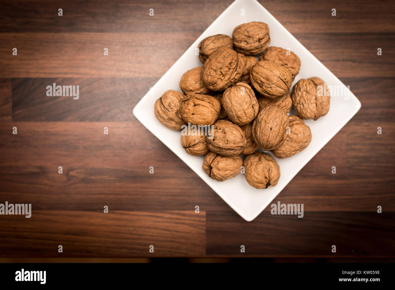 A bowl of whole walnuts in their shells in a bowl shot from above on a black slate background Stock Photo