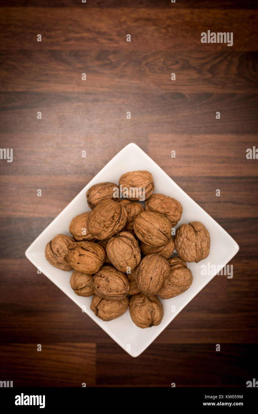A bowl of whole walnuts in their shells in a white square bowl shot from above on a butchers block worktop - Stock Image
