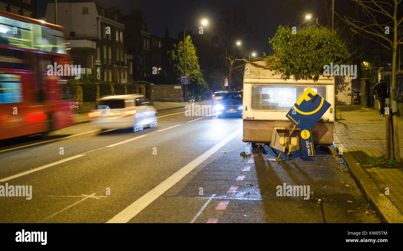 London, England - 29 December 2014: A derelict caravan abandoned on Brixton Road in South London is adorned with - Stock Image