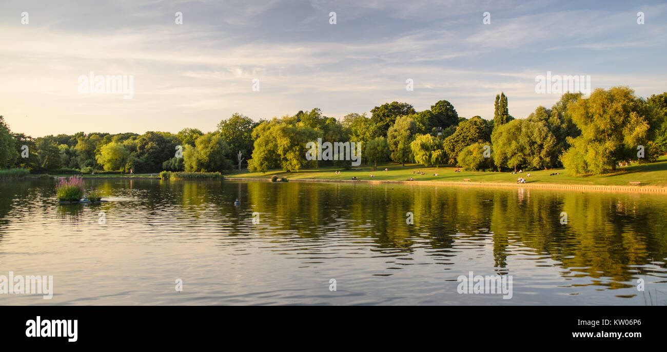 London, England, UK - August 20, 2013: People relax beside the Hampstead Ponds in Hampstead Heath park, North London. Stock Photo