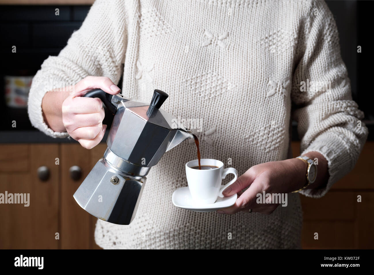 A smart but casually dressed woman pouring an espresso coffee from a moka hob espresso maker whilst standing in - Stock Image
