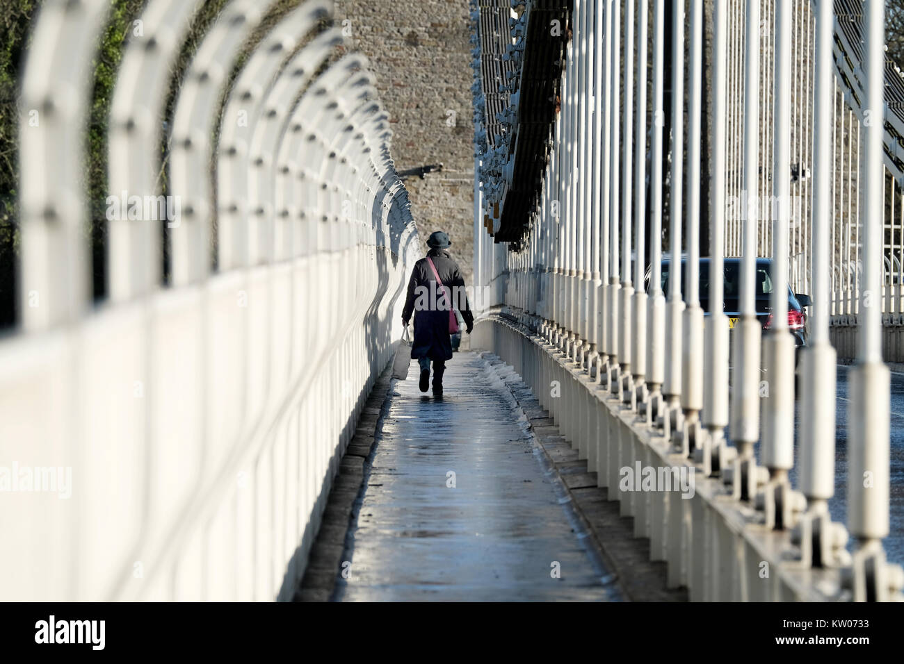 A woman carrying a large bag walking across the Clifton Suspension Bridge in Bristol, UK. A cold winter day and - Stock Image