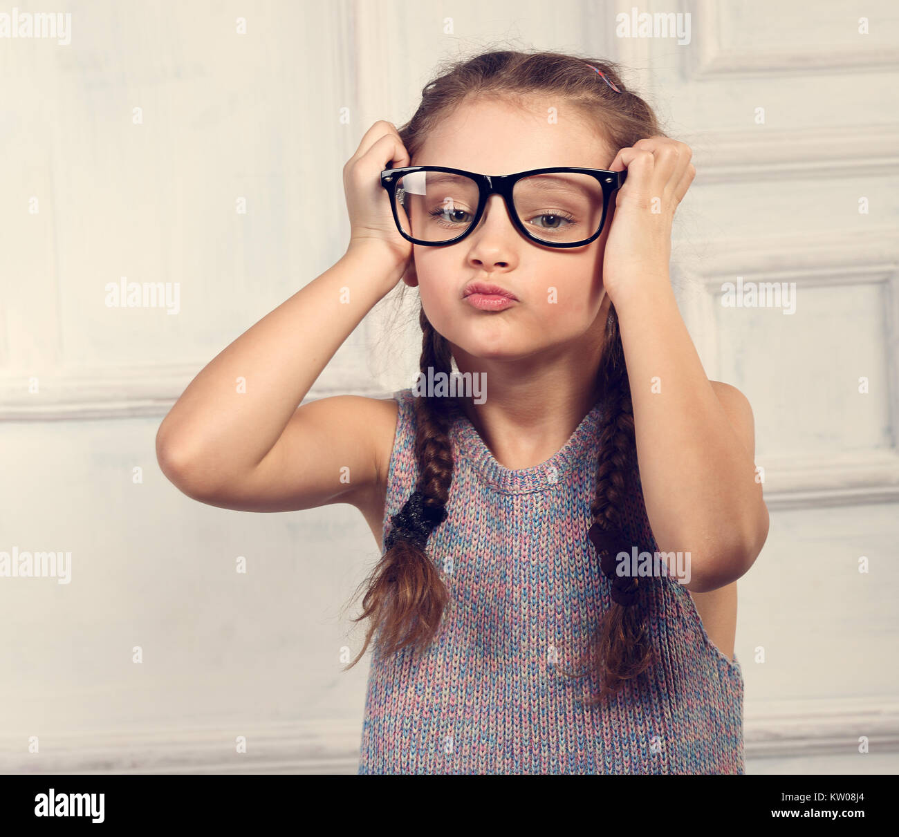 d26ef97a1b Happy fun kid girl holding fashion glasses with excited emotional face  looking on blue studio background