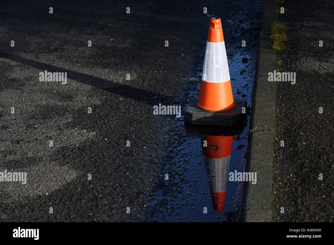 A single traffic cone pictured with reflection in West Sussex, UK. - Stock Image