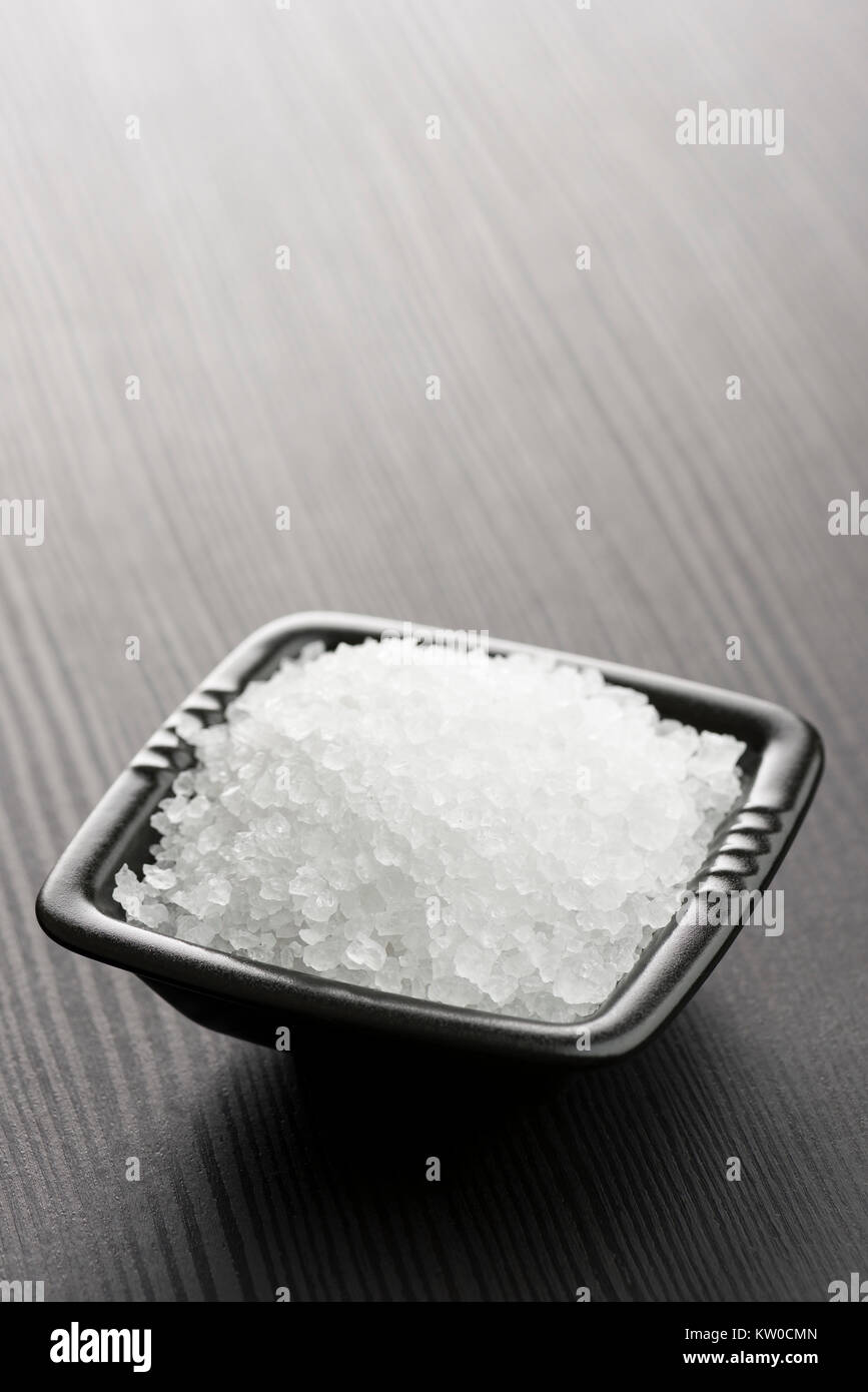 natural salt into black bowl on wooden table - Stock Image