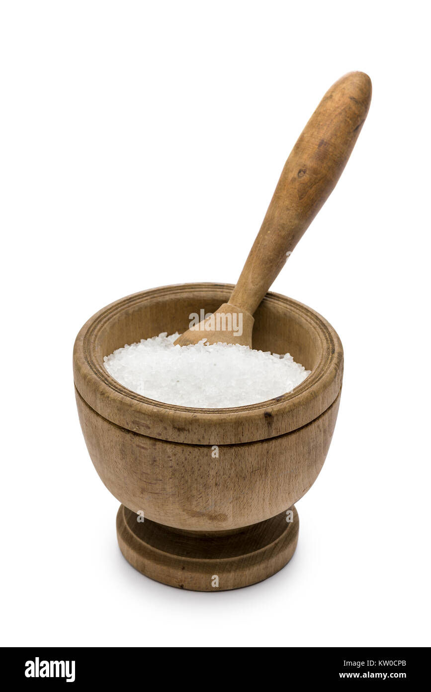 natural salt into wooden pestle, on white background - Stock Image