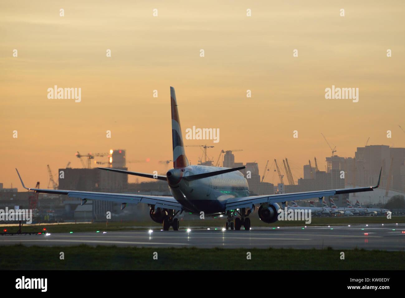 British Airways BA CityFlyer Embraer taxing at London City Airport at dusk - Stock Image