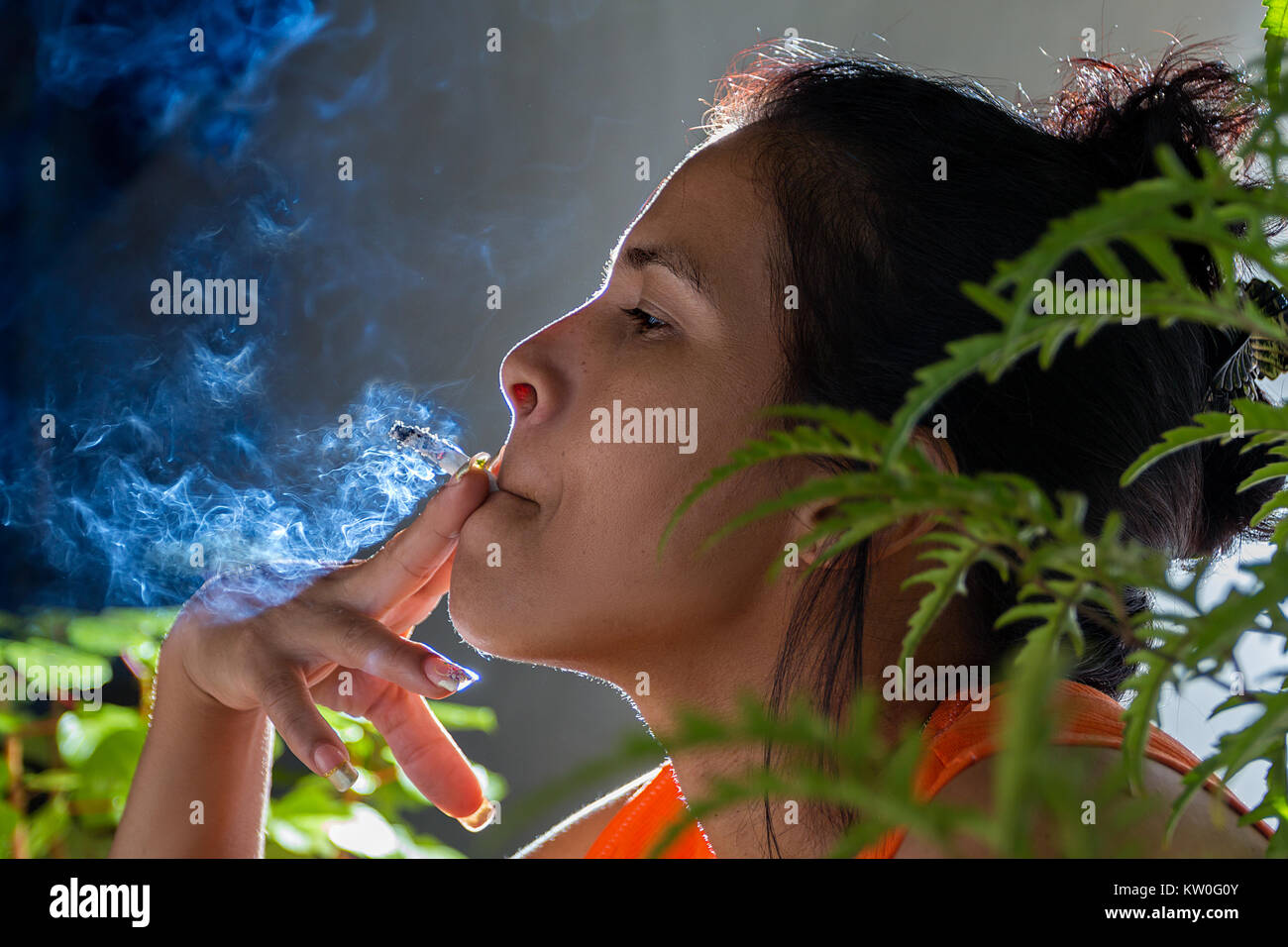 A latin woman smoking, holding a cigarette with her finger and her mouth - Stock Image