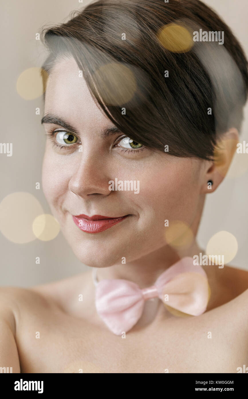 Young woman face with lights bokeh on foreground. Christmas style portrait of the young girl with a pink bow tie - Stock Image