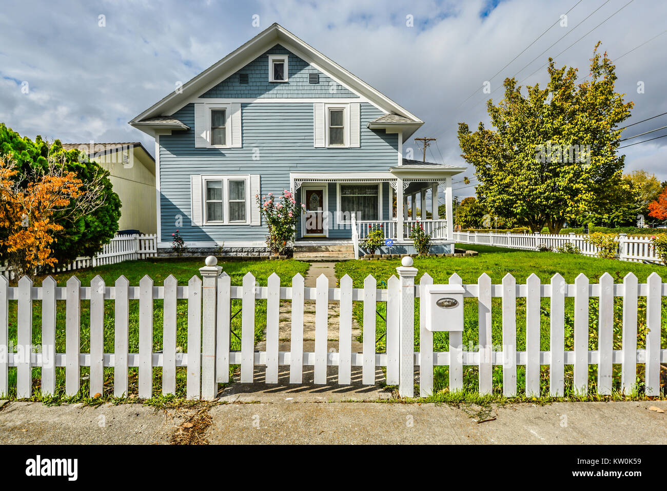 Cute, quaint vintage home with a small garden, covered front porch and white picket fence in the American Northwest - Stock Image