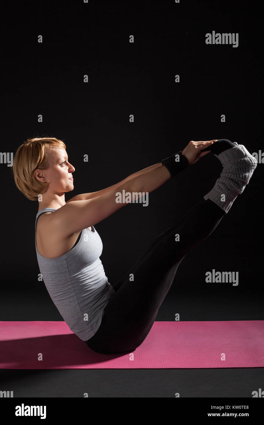 Young woman practicing yoga, Ubhaya Padangusthasana, Both Big Toes Pose - Stock Image