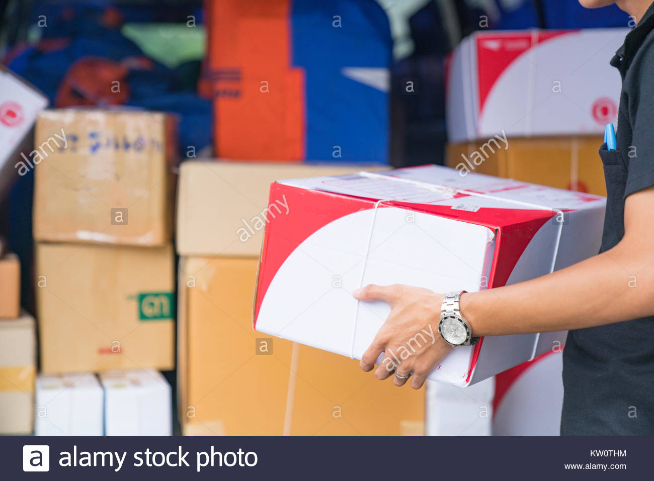 Delivery A man carrying package from delivery car - courier service concept - Stock Image