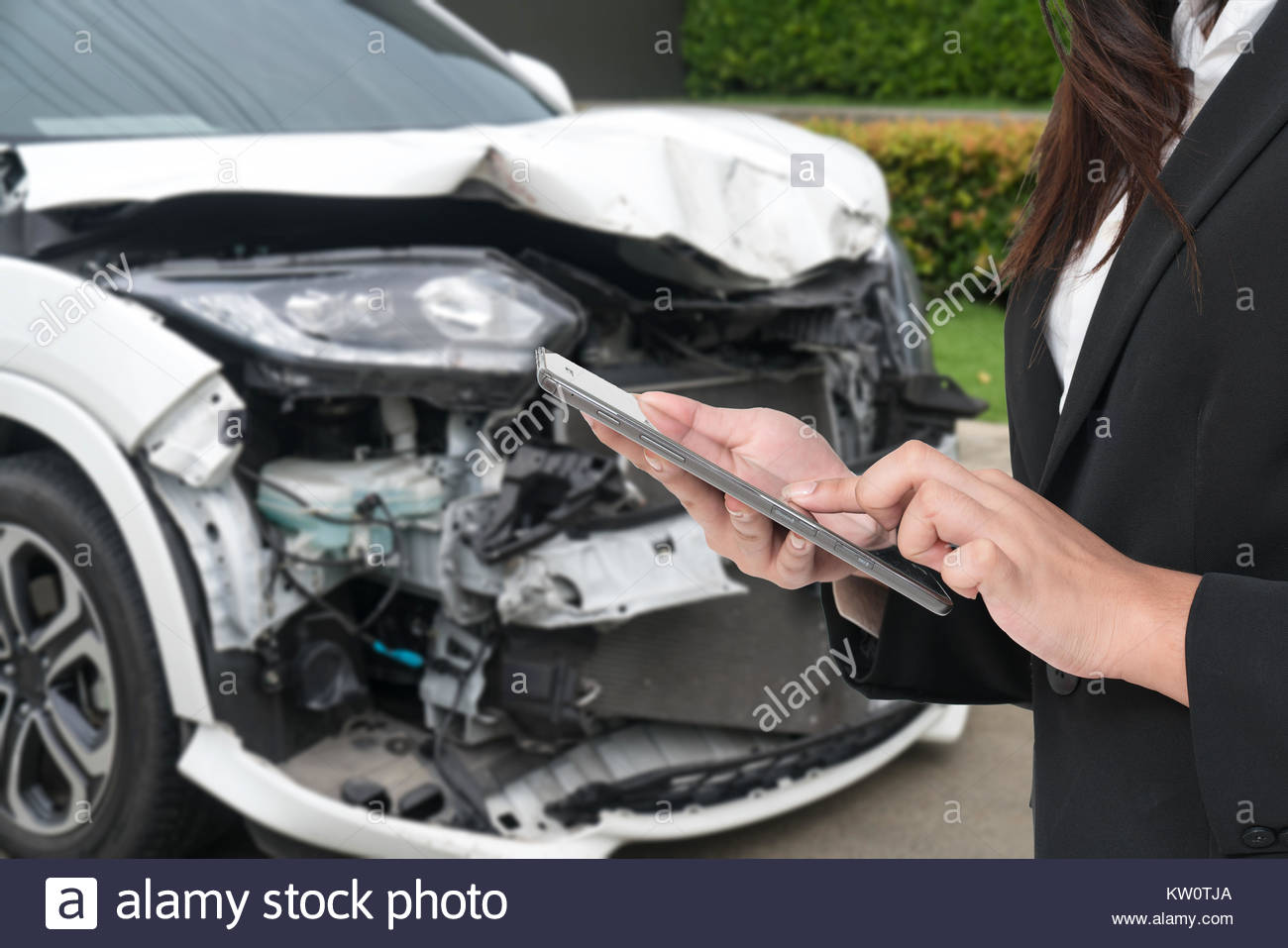 Insurance Agent Inspecting Damaged Car With Insurance Claim Form On Digital Tablet - Stock Image